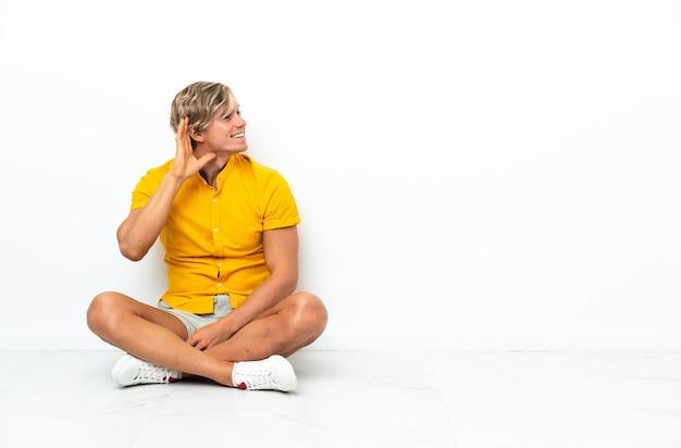 Jonge engelse man zittend op de vloer luisteren naar iets door hand op het oor te leggen