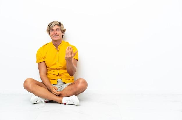 Jonge engelse man zittend op de vloer uitnodigend om met de hand te komen. blij dat je gekomen bent