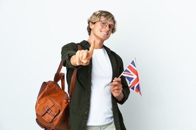 Jonge engelse vrouw die een vlag van het verenigd koninkrijk houdt en een vinger opheft