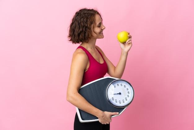 Jonge engelse vrouw die op roze muur met weegmachine en met een appel wordt geïsoleerd