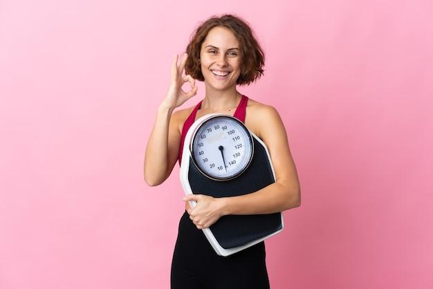 Jonge engelse vrouw die op roze muur wordt geïsoleerd die een weegmachine houdt en ok teken doet