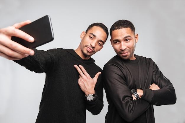 Jonge ernstige afrikaanse mannen maken een selfie.