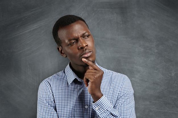 Jonge ernstige afrikaanse zakenman in overhemd, hand in hand op zijn kin, kijkt met een bedachtzame en sceptische uitdrukking op zijn gezicht, vermoedt iets, aarzelt om een beslissing te nemen.