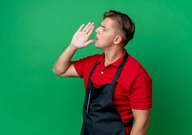Jonge ernstige blonde mannelijke kapper in uniform kijkt kant doet alsof hij iemand belt die hand dicht bij de mond houdt geïsoleerd op groene ruimte met kopie ruimte
