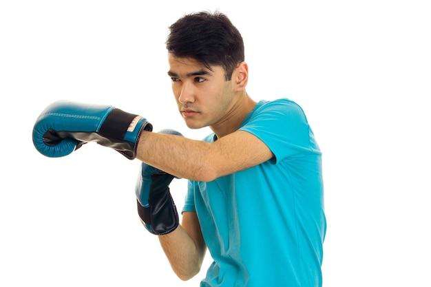 Jonge ernstige brunette man in blauwe bokshandschoenen oefenen geïsoleerd op een witte muur Premium Foto