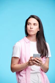 Jonge ernstige brunette vrouw in vrijetijdskleding opzij kijken tijdens het scrollen in smartphone geïsoleerd