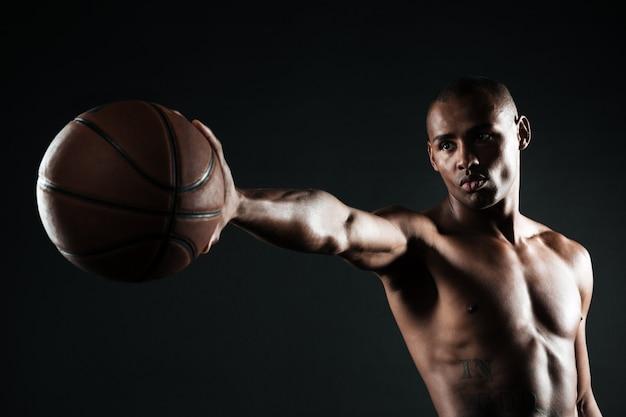 Jonge ernstige de holdingsbal van de basketbalspeler met één hand