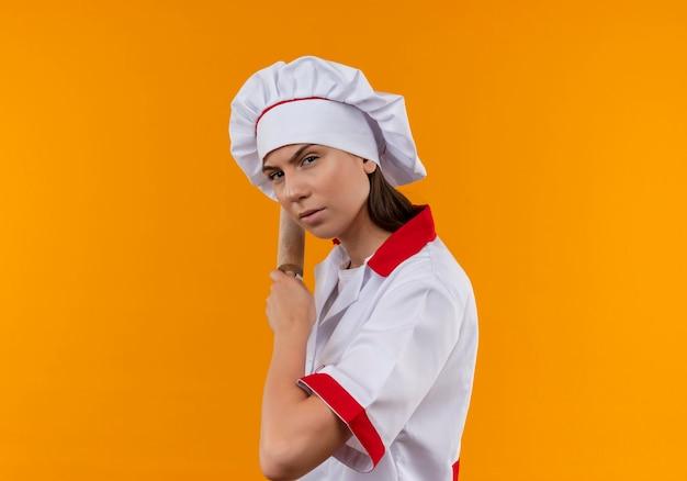Jonge ernstige kaukasisch kok meisje in uniform chef staat zijwaarts en houdt deegroller achter op oranje met kopie ruimte