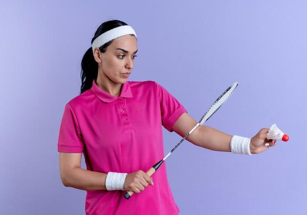 Jonge ernstige kaukasische sportieve vrouw die hoofdband en polsbandjes draagt houdt en kijkt naar het racket van de shuttleholding op paars met exemplaarruimte