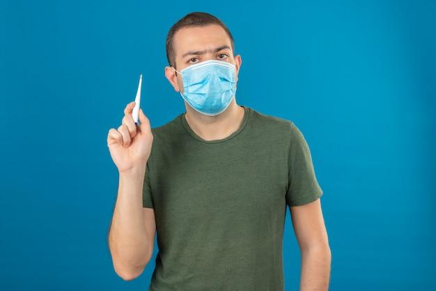 Jonge ernstige kijkende mens die gezichts medisch masker dragen die een digitale thermometer houden in het opheffen van hand op blauw wordt geïsoleerd