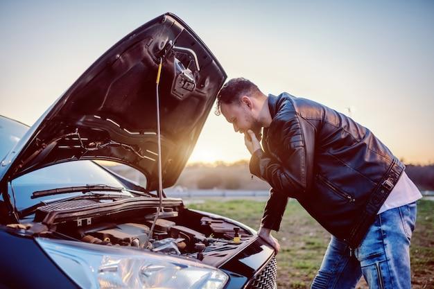 Jonge ernstige knappe kaukasische bebaarde blonde man in lederen jas op zoek motor van zijn auto onder de motorkap. er is iets fout gegaan.