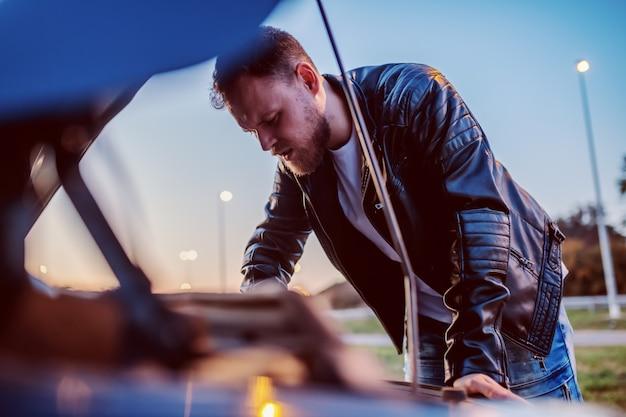 Jonge ernstige knappe kaukasische bebaarde blonde man in leren jas motor van zijn auto onder de motorkap controleren.