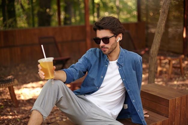 Jonge ernstige knappe man in vrijetijdskleding lunchpauze, glas ijsthee houden zittend in de openbare tuin, luisteren naar muziek met oortelefoons