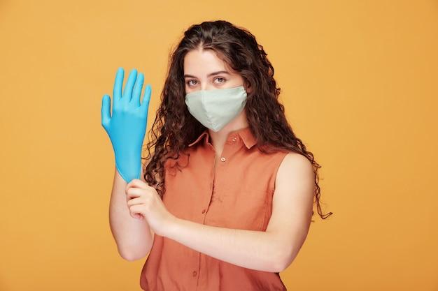 Jonge ernstige mooie vrouw in overhemd en beschermend masker blauwe handschoenen aantrekken om covid19-infectie te vermijden in de quarantaineperiode