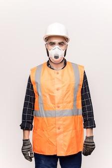 Jonge ernstige technicus in oranje werkkleding, beschermende handschoenen, brillen en gasmasker