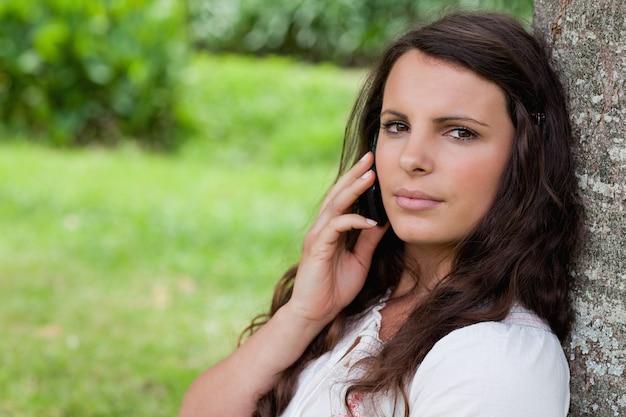 Jonge ernstige vrouw die met haar mobiele telefoon roept terwijl het zitten tegen een boom