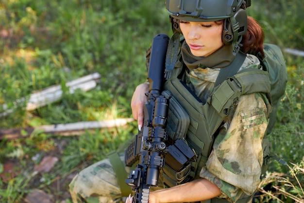Jonge ernstige vrouw in militaire slijtage zit op gras te wachten op vijand aan de zijkant