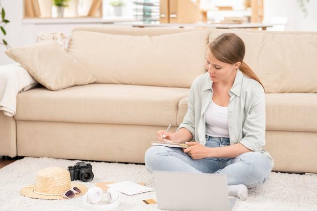 Jonge ernstige vrouw in vrijetijdskleding, zittend op de vloer voor laptop en het maken van een lijst met dingen die u mee moet nemen voor de reis