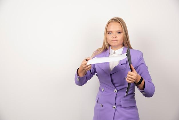 Jonge ernstige vrouw met potlood en tablet op wit.