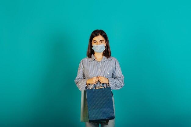 Jonge ernstige vrouw met veelkleurige pakketten maken winkelen.