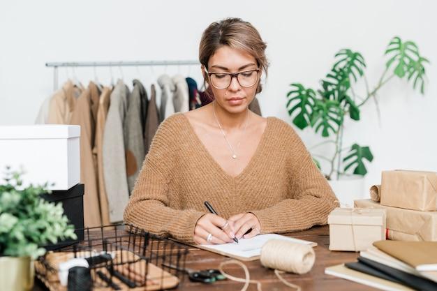 Jonge ernstige vrouwelijke klant in brillen en pullover lijst van bestelde goederen controleren en teken zetten met zwarte markeerstift