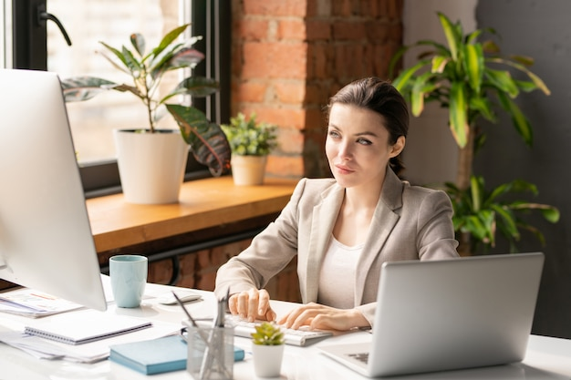 Jonge ernstige vrouwelijke makelaar in formalwear die gegevens op computerscherm doorzoeken terwijl door bureau in bureau zit