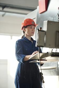Jonge ernstige werkneemster in uniform en helm scherm van het configuratiescherm kijken tijdens het werken met technische gegevens