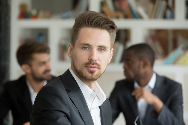 Jonge ernstige zakenman die camera op vergadering, headshotportret bekijkt