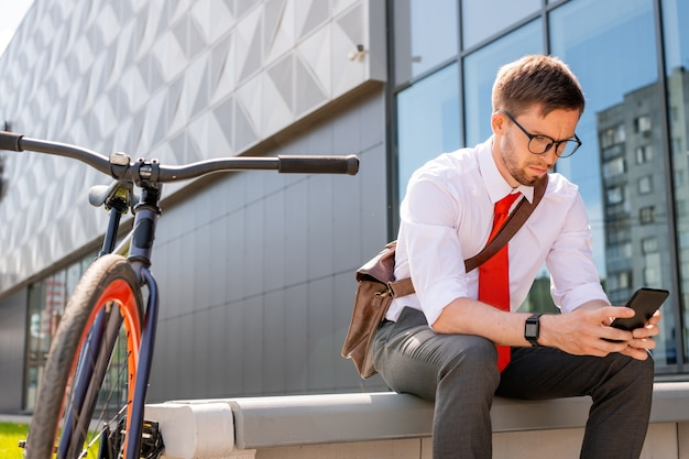 Jonge ernstige zakenman smartphonescherm kijken tijdens het scrollen door berichten tijdens pauze in het midden van de werkdag