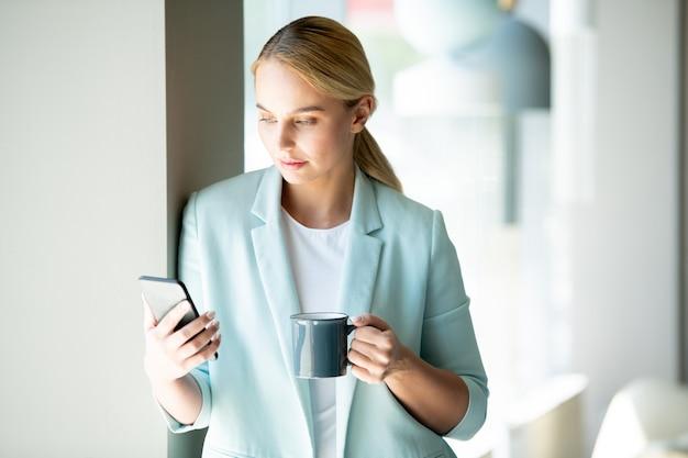 Jonge ernstige zakenvrouw kijken naar video in smartphone of bericht of bericht lezen door drankje in café