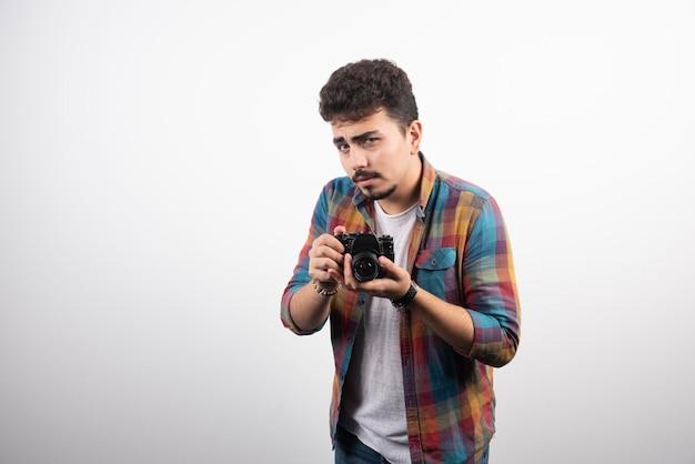 Jonge ervaren foto die op een serieuze manier professionele foto's maakt.
