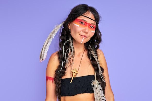 Jonge etnische dame met veren op haar hoofd geïsoleerd over paarse muur, vrouw in top, sjamaan glimlacht