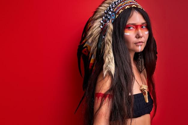 Jonge etnische dame met voorn op haar hoofd geïsoleerd over rode muur, vrouw in top, sjamaan