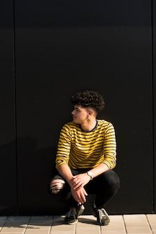 Jonge etnische krullende man zit tegen zwarte muur