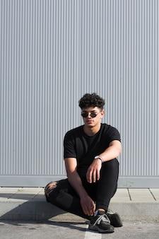 Jonge etnische mens die in zonnebril tegen grijze muur zit