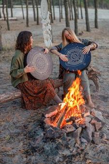 Jonge etnische volwassen sjamaan vrouw loopt en speelt meditatieve muziek op drums
