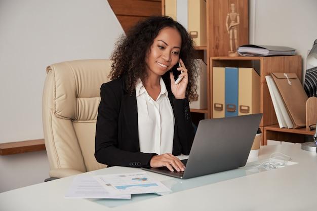 Jonge etnische vrouw die op telefoon in bureau spreekt