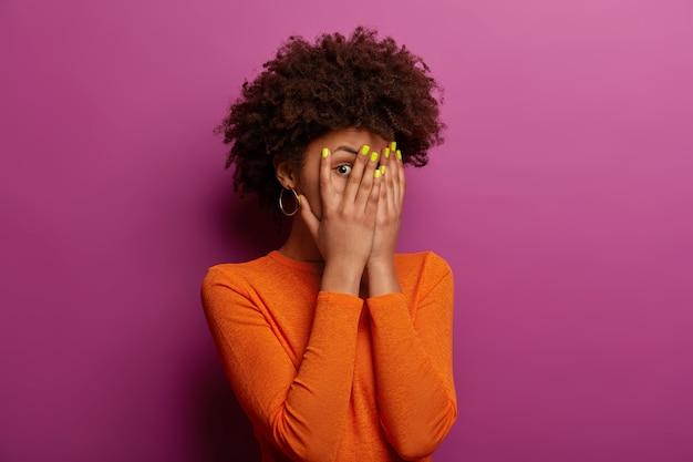 Jonge etnische vrouw gluurt door vingers, verbergt gezicht met handpalmen