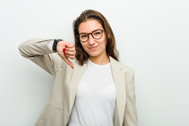 Jonge europese bedrijfsvrouw die een afkeergebaar, duimen neer toont. meningsverschil concept.