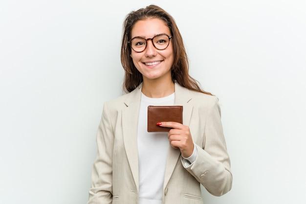 Jonge europese bedrijfsvrouw die een portefeuille gelukkig, glimlachend en vrolijk houdt.