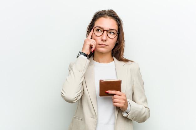 Jonge europese bedrijfsvrouw die een portefeuille houdt die haar tempel met vinger richt, het denken, concentreerde zich op een taak.
