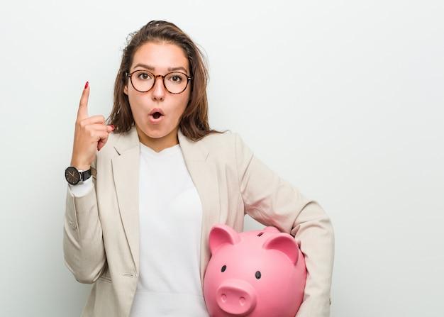 Jonge europese bedrijfsvrouw die een spaarvarken houdt dat één of ander groot idee, creativiteit heeft.
