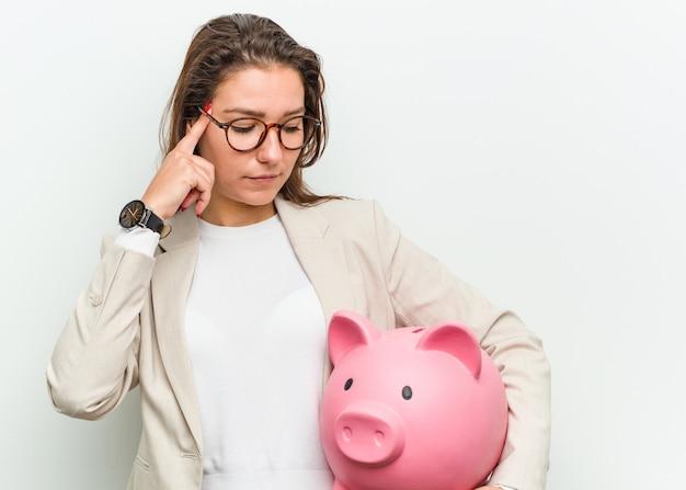 Jonge europese bedrijfsvrouw die een spaarvarken houdt dat haar tempel met vinger richt, denkt, concentreerde zich op een taak.