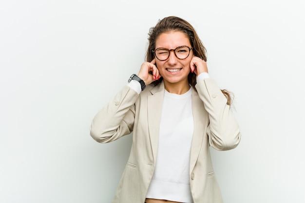 Jonge europese bedrijfsvrouw die haar oren behandelt met haar handen