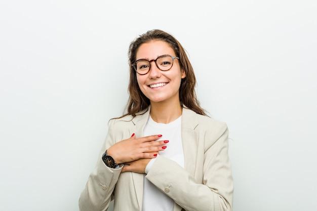 Jonge europese bedrijfsvrouw die houdend haar handen op hart lacht