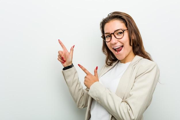 Jonge europese bedrijfsvrouw die met wijsvingers aan een exemplaar richt, opwinding en wens uitdrukt.