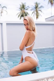 Jonge europese blonde haar fit vrouw in witte zwembroek staat in lichtblauwe kleur zwembad natuurlijke daglicht houdt kokosnoot plastic stro