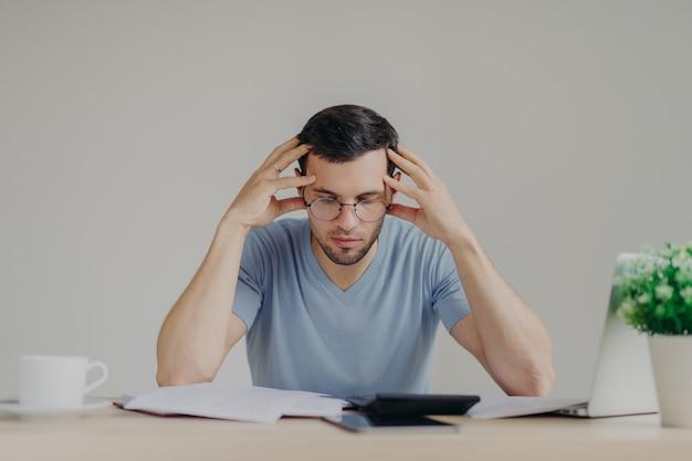 Jonge europese man die nonchalant gekleed is, heeft schuldenproblemen en kan niet alle schulden betalen