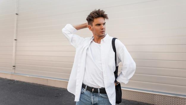 Jonge europese man met een kapsel in een modieus shirt in spijkerbroek met een zwarte stoffen tas vormt in een modern gebouw buiten in de stad.