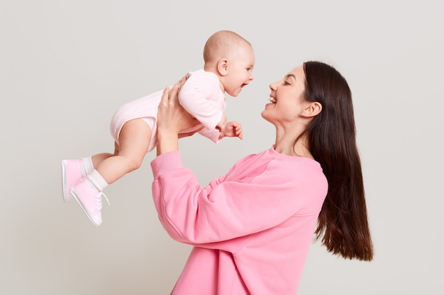 Jonge europese moeder haar babymeisje in handen houden en kijken naar haar baby met liefde en zachte glimlach, vrouw met donker haar roze casual trui dragen, spelen met haar kind.